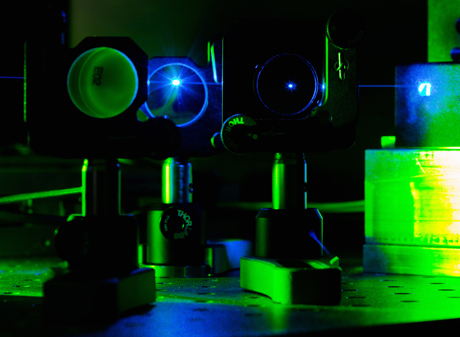This picture shows a green and blue shining optical equipment of the laser scanning microscopy.